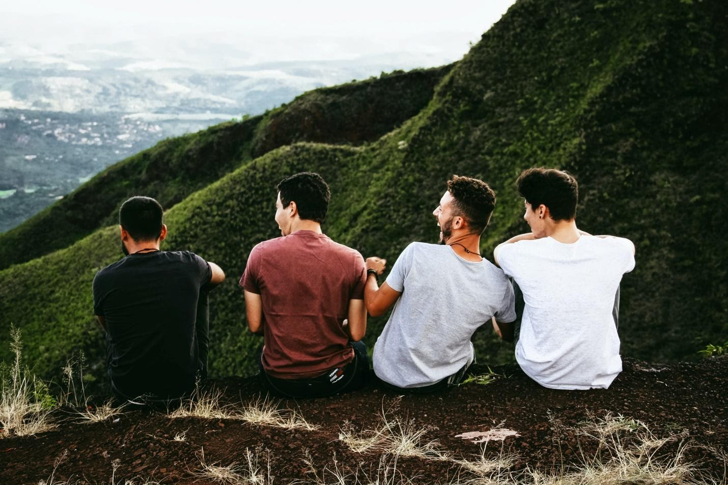 male friends sitting on a cliff